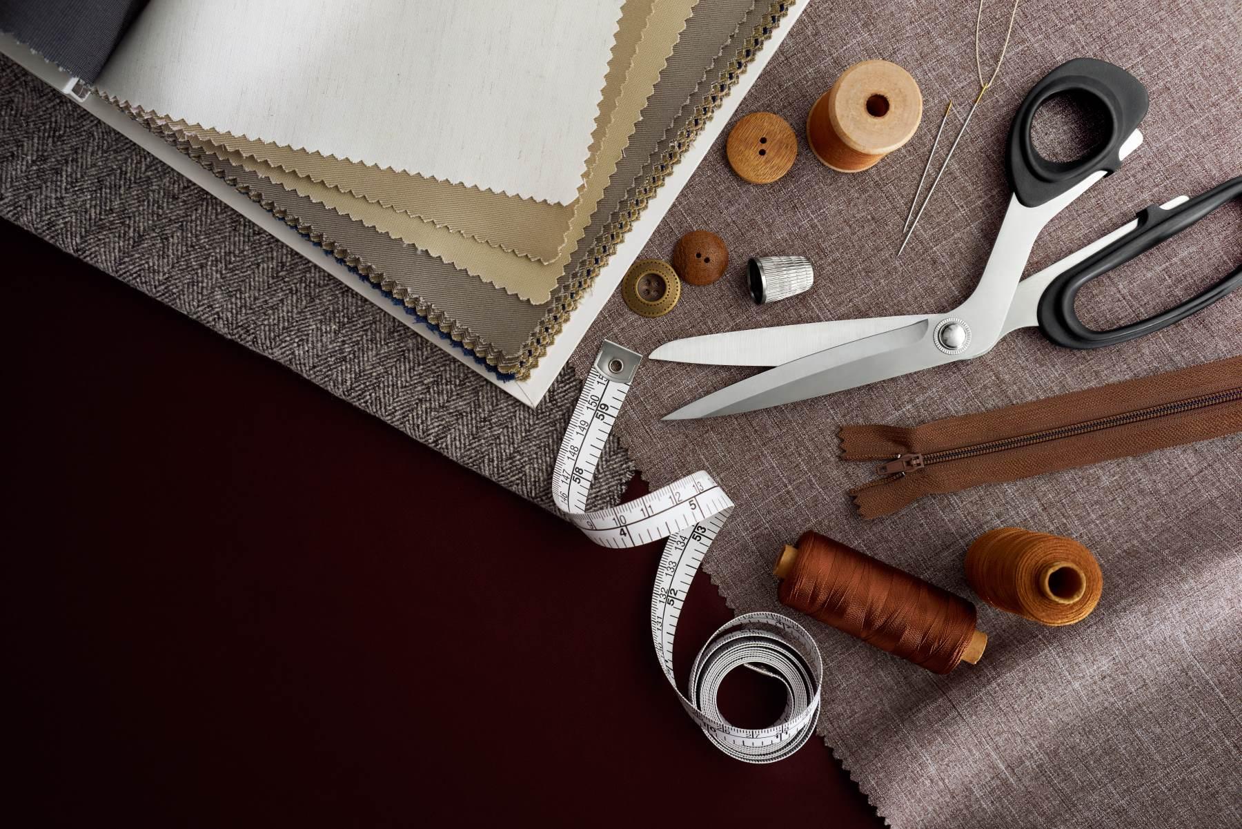 Forbici, bottoni, zip, misura a nastro, filettatura e tamburo su tessuti