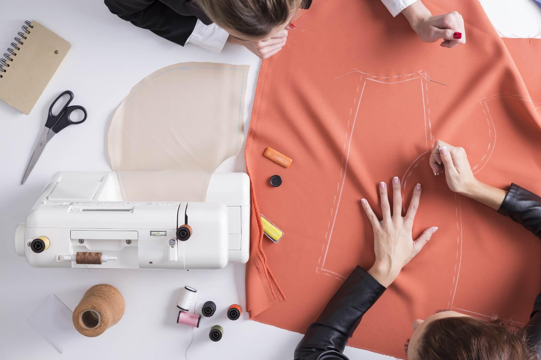 Due ragazze che fanno un modello su un pezzo rosso di materiale
