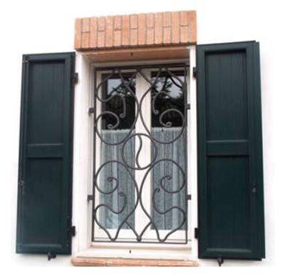 una finestra con una griglia in ferro battuto con forme a spirale e le ante delle persiane verdi scure aperte
