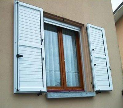 una finestra con le ante delle persiane di color bianco aperte