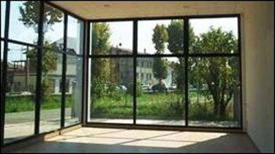 vista dall'interno di un appartamento circondato da vetrate con finiture nere