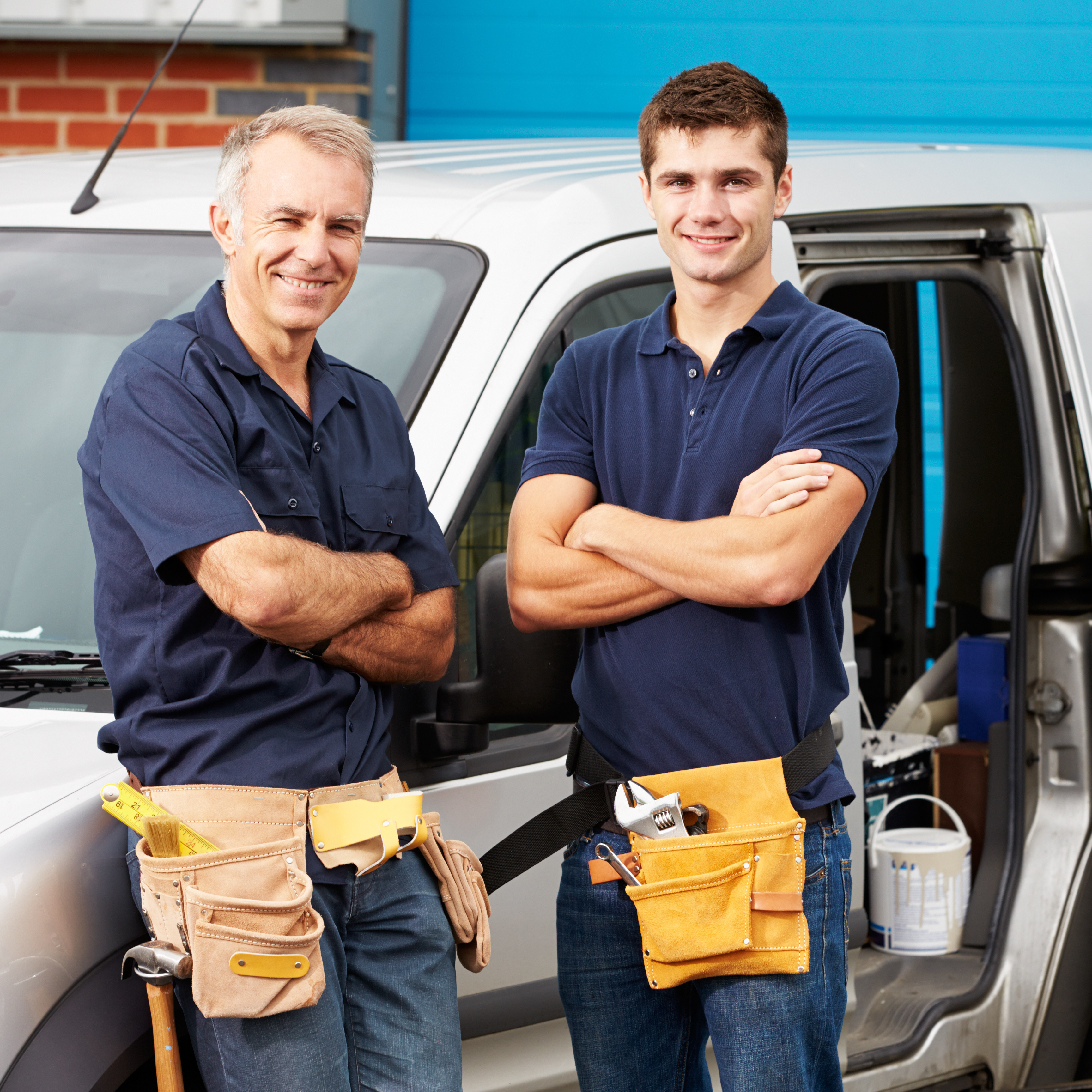 Plumbers standing by their truck