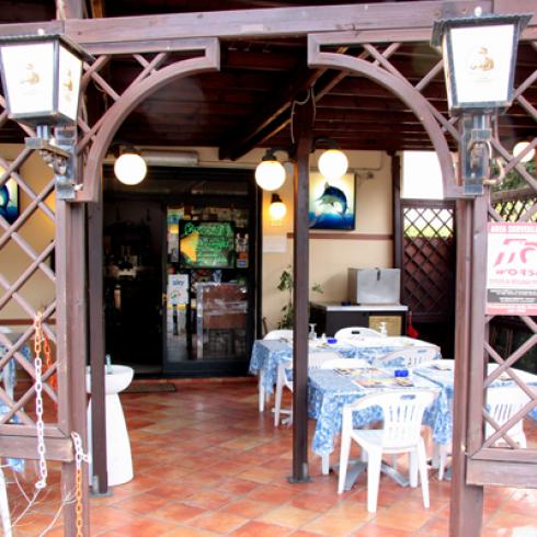 un arco in legno, due lampioni e vista dei tavoli