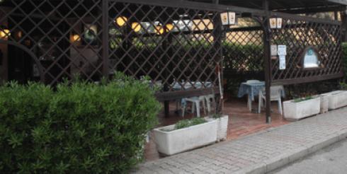 una siepe, dei vasi di fiori e vista dei tavoli
