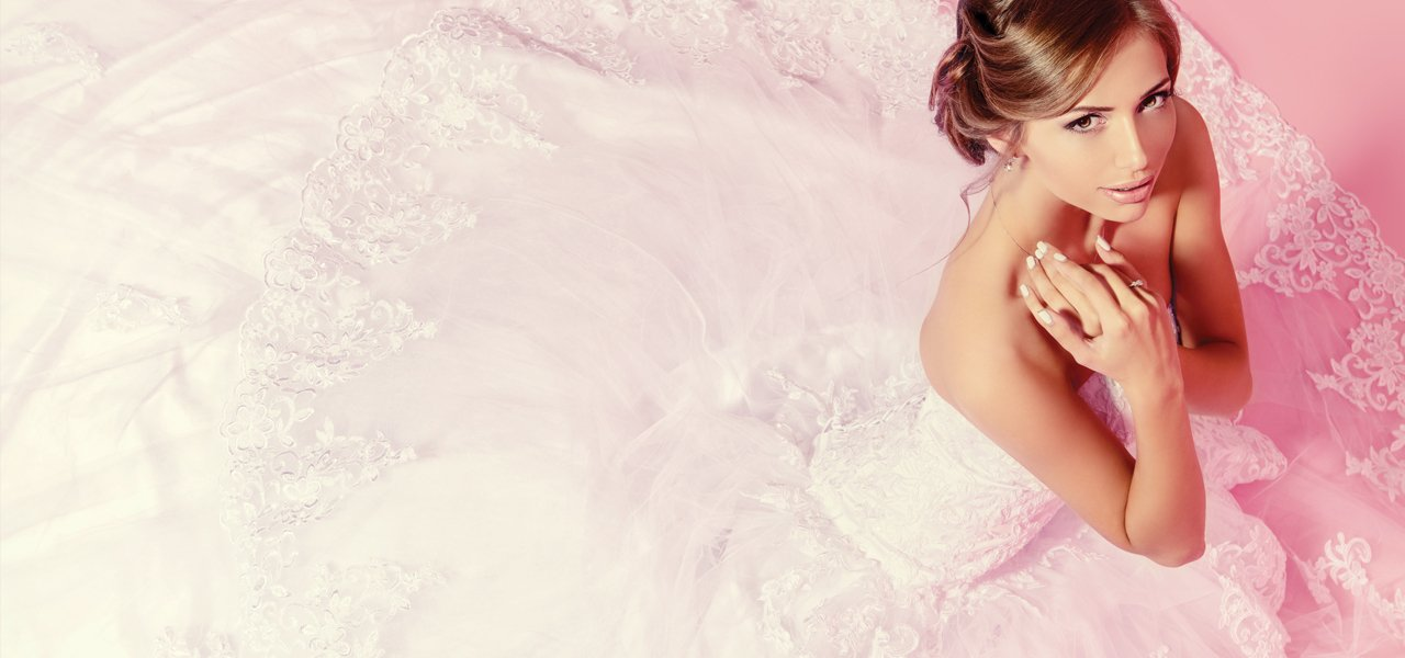 A woman sat on the floor in a pink wedding dress