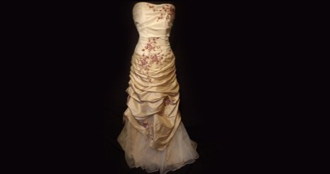 A cream wedding dress covered in decorative flowers