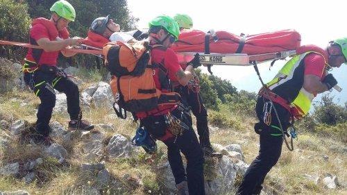 dei soccorritori con un imbracature mentre trasportano una barella con un uomo