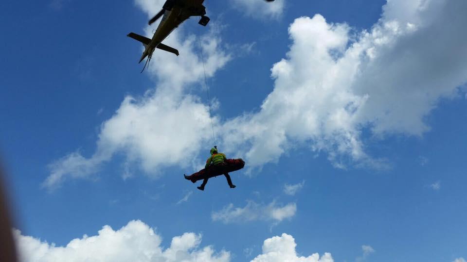 un soccorritore con in mano una barella con un uomo e un imbracatura con una fune appesa all'elicottero