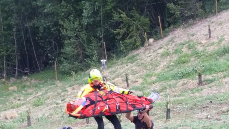 un soccorritore con in mano una barella legata a una fune