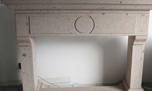 una struttura in marmo con due colonne e un disegno circolare scavato al centro