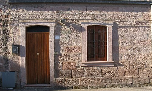 una casa in pietra con una porta e una finestra di legno
