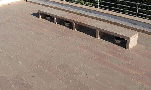 una pavimentazione in mattoni rosa e una struttura di mattoni simile a una panchina