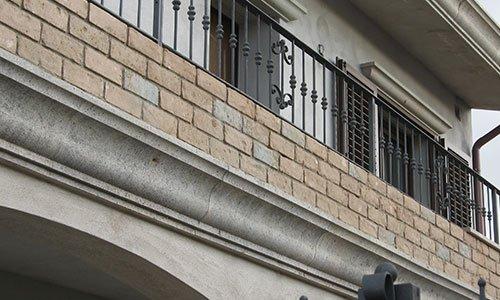 vista di un balcone con ringhiera in ferro battuto e sotto dei mattoni arancioni e grigi in pietra