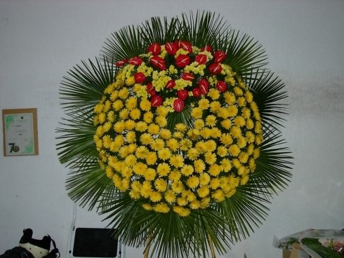allestimento di fiori gialli e rossi per funerale
