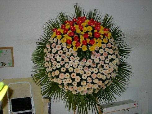 allestimento di fiori bianchi, gialli e rossi per cerimonia funebre
