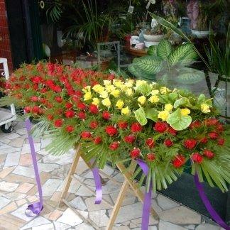 allestimento rose rosse e gialle per cofano funebre