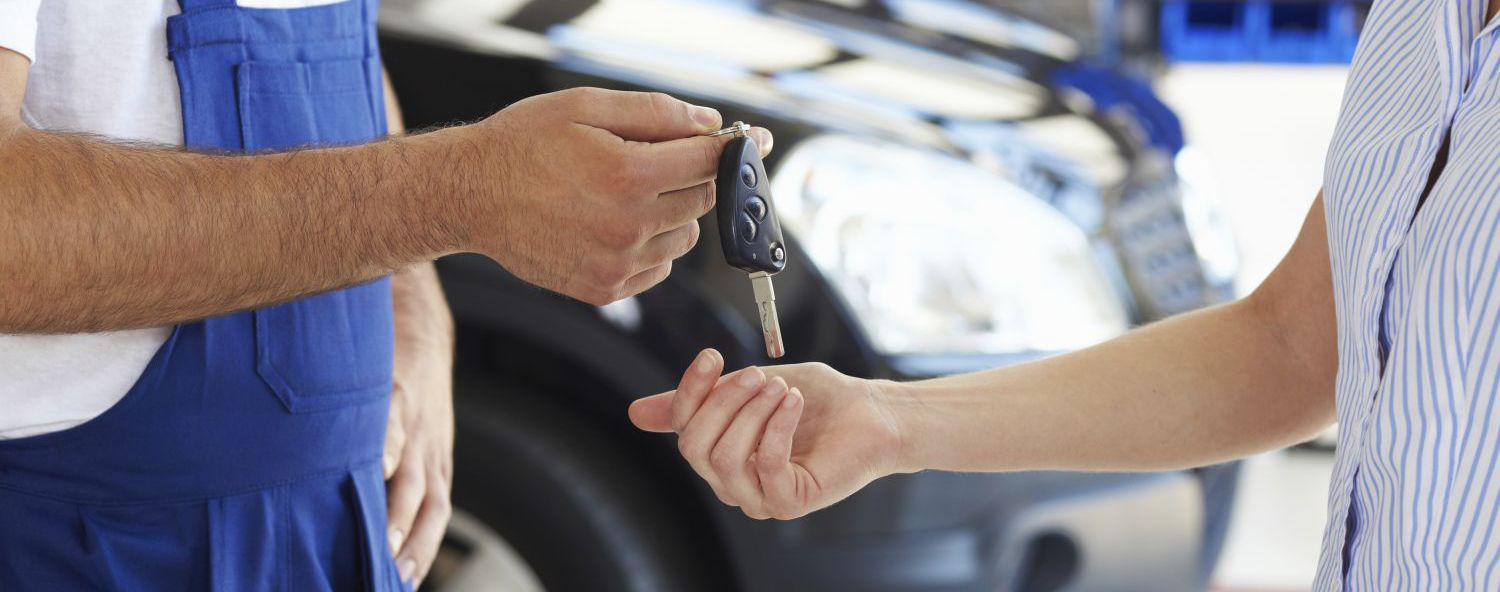 mechanic at automobile boy repair shop at Auckland  returning keys to customer