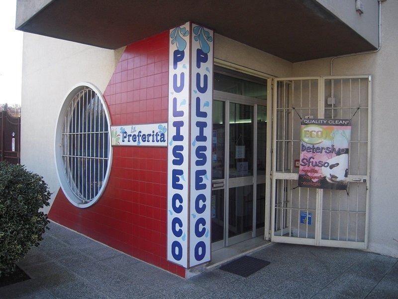 vista dall'esterno della lavanderia con mattoni rossi e la scritta Pulisecco
