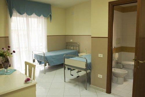 una camera con due letti ospedalieri, una scrivania e vista di un bagno