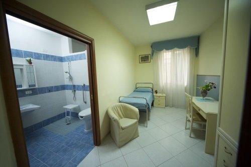 una camera con un letto, una scrivania e vista di un bagno