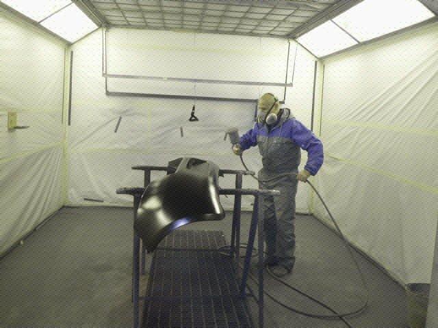 Operaio vernicia la parte di una carrozzeria nel forno verniciatura