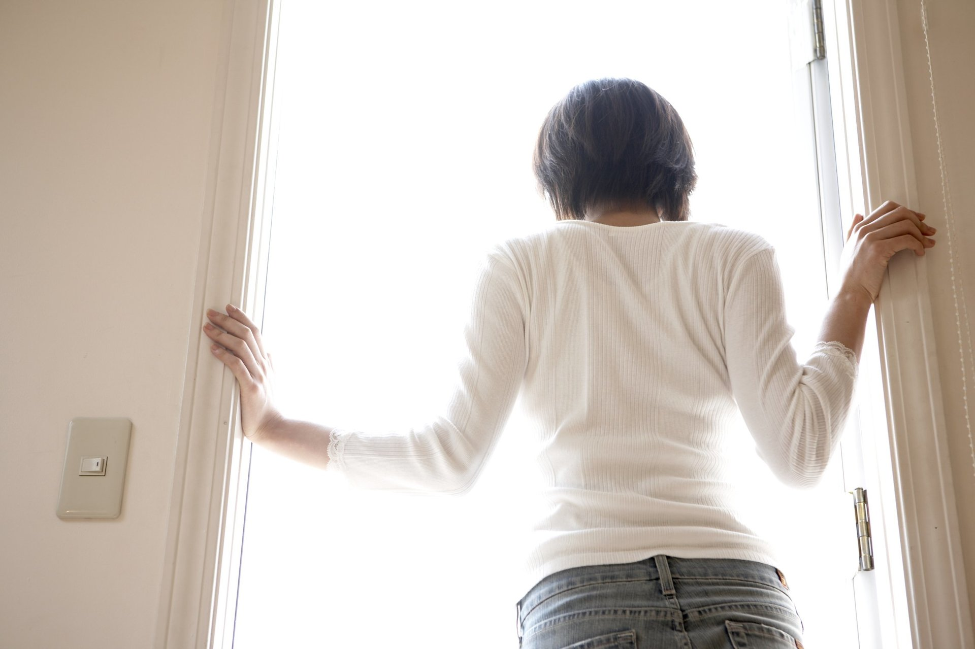 una donna  davanti a una porta finestra aperta