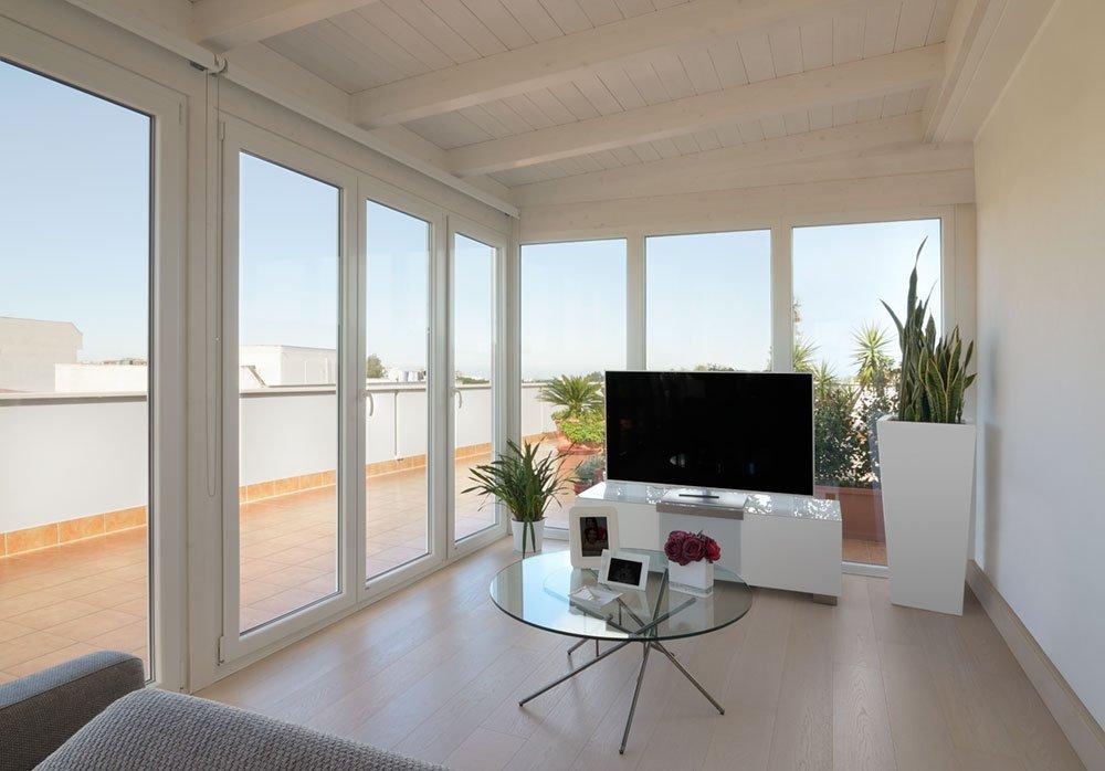 Una sala moderna con un tavolino di vetro e un mobile con una tv