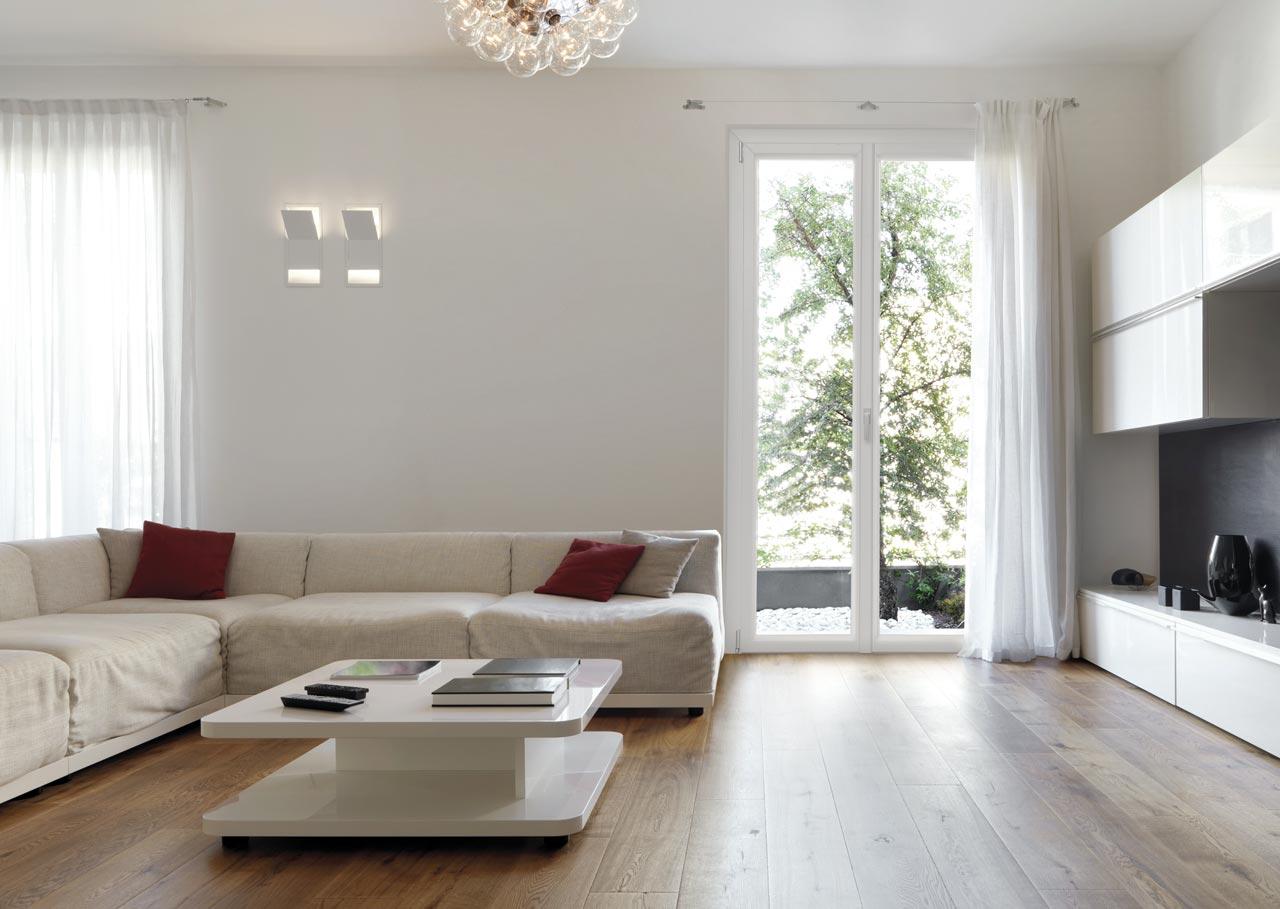 Un salotto con un divano bianco angolare e un tavolino al centro