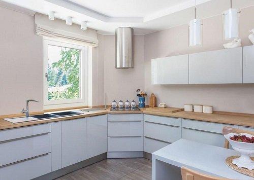 Una cucina angolare con mobili bianchi e top marrone