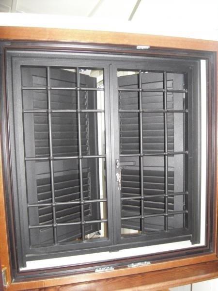 Una finestra con delle persiane nere e una griglia