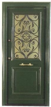 Una porta in legno color verde con finiture in ferro battuto al centro