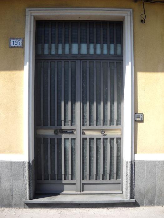 portale in pietra lavica e pietra di comiso con cornice a rilievo