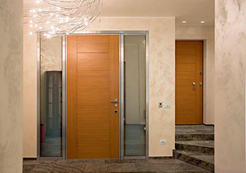 Una porta in legno chiaro con dei  vetri sui lati