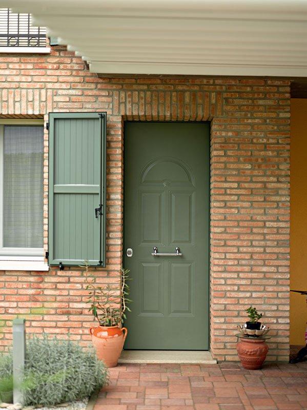Una porta e una finestra di color verde salvia