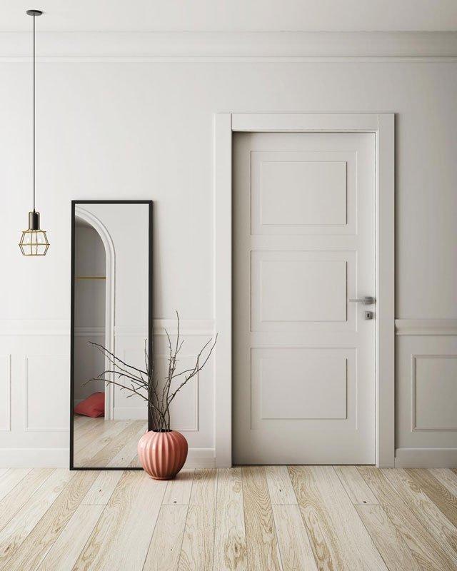 Una porta di color bianco e sulla sinistra uno specchio lungo