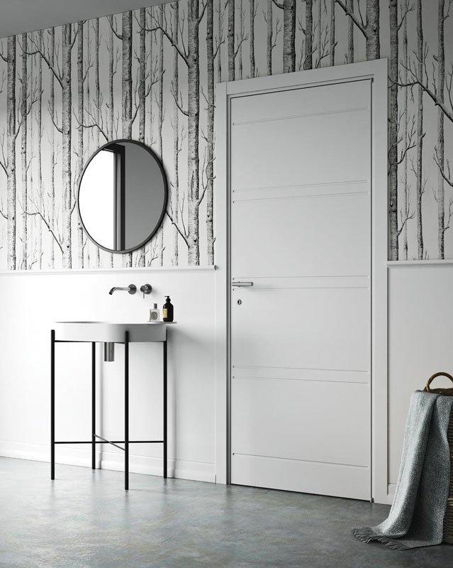 Una porta di color bianco e sulla sinistra una console con sopra uno specchio rotondo