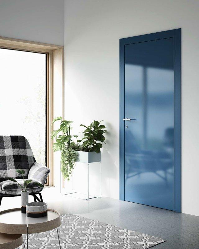 Una porta di color blu sulla destra e accanto un vaso con delle piante