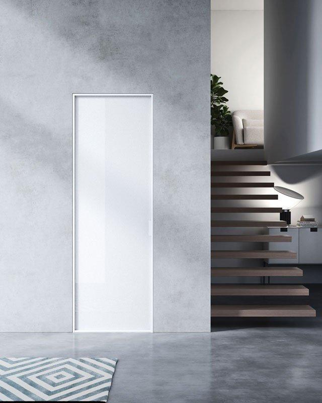 Delle scale in legno senza corrimano e una porta di color bianco