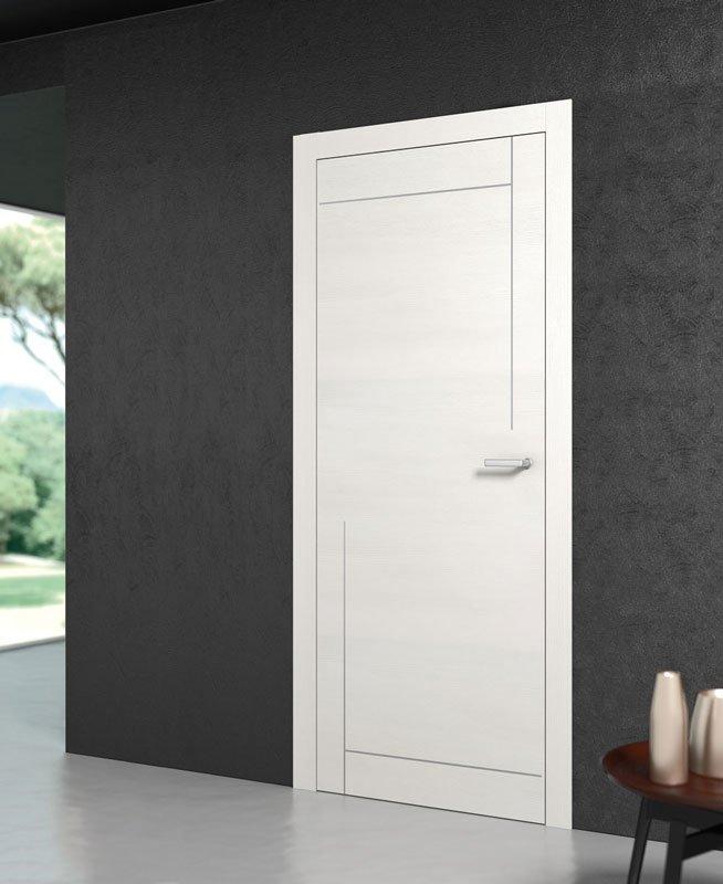 Una porta di color bianco e dei muri di color grigio scuro e un tavolino sulla destra