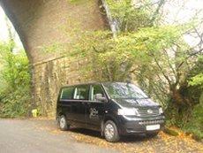 black VW minibus under a bridge