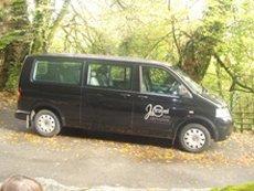 our black VW minibus under trees in sunshine