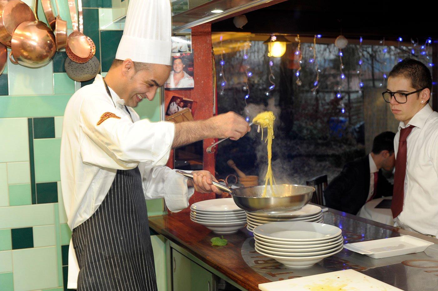 Un cuoco mentre serve degli spaghetti in un piatto