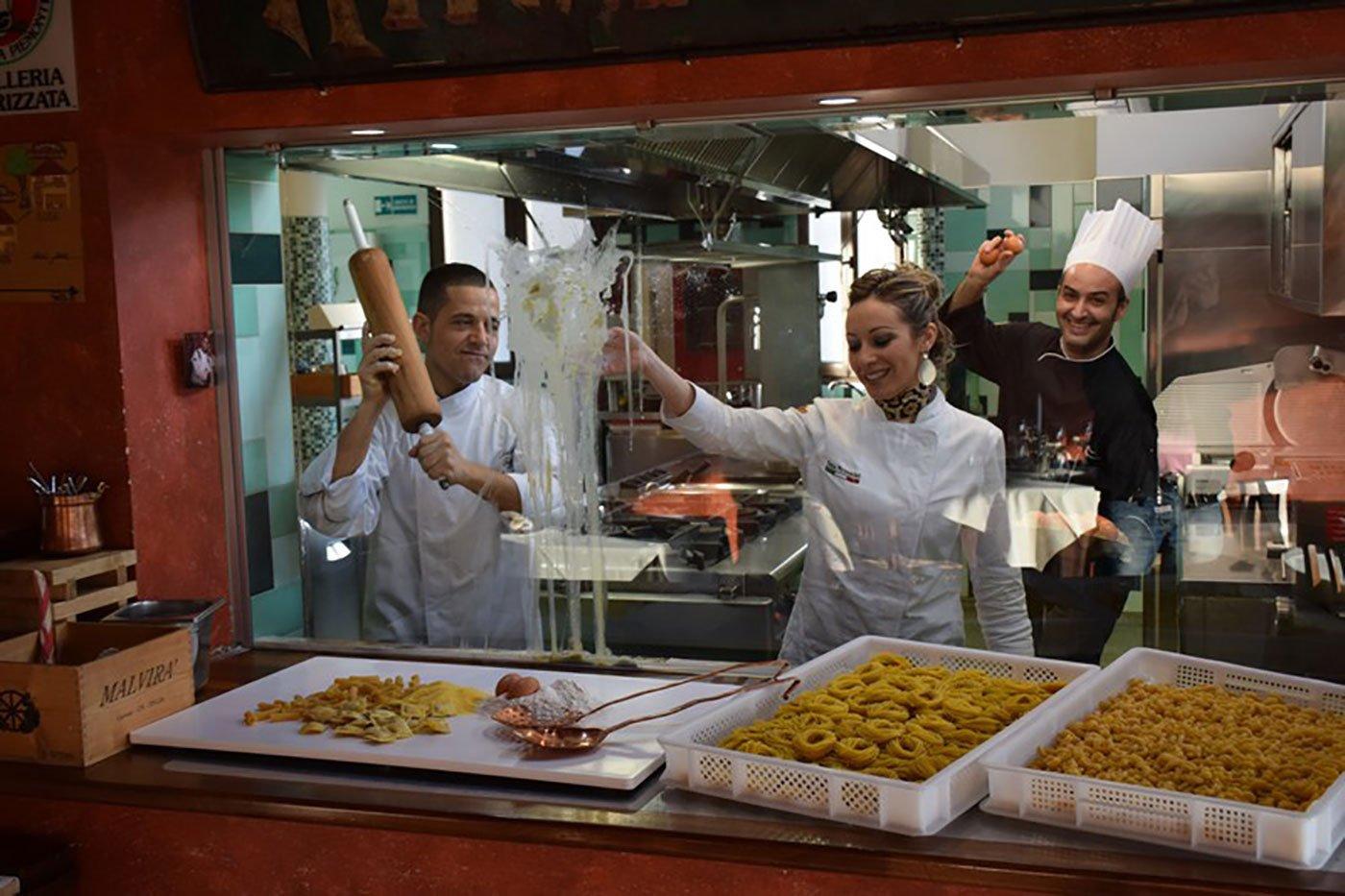 Tre cuochi in una cucina con dei vassoi di pasta fresca