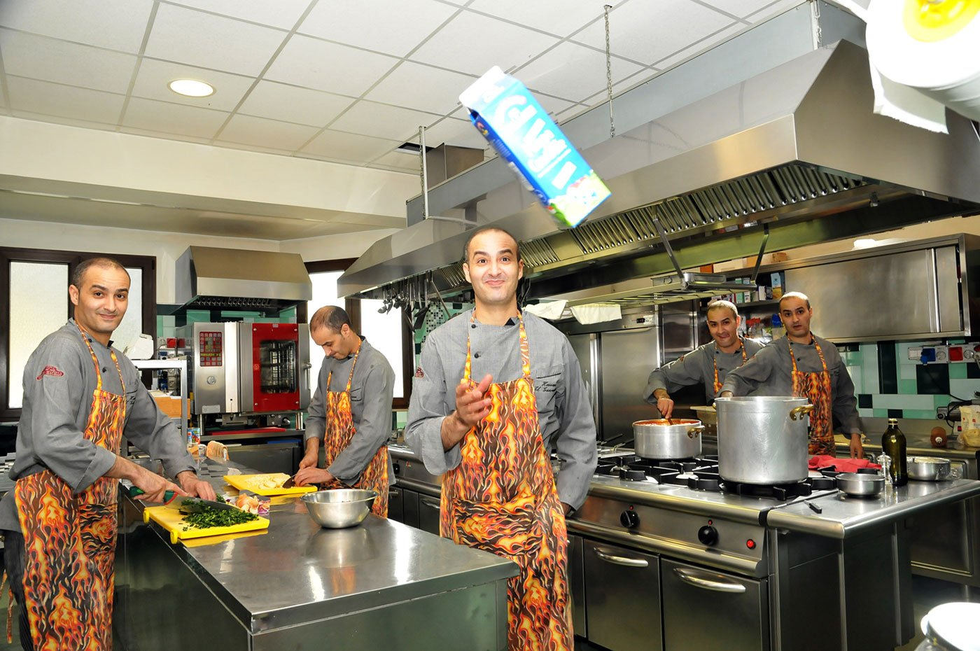Un'immagine raffigurante un cuoco in azione in una cucina
