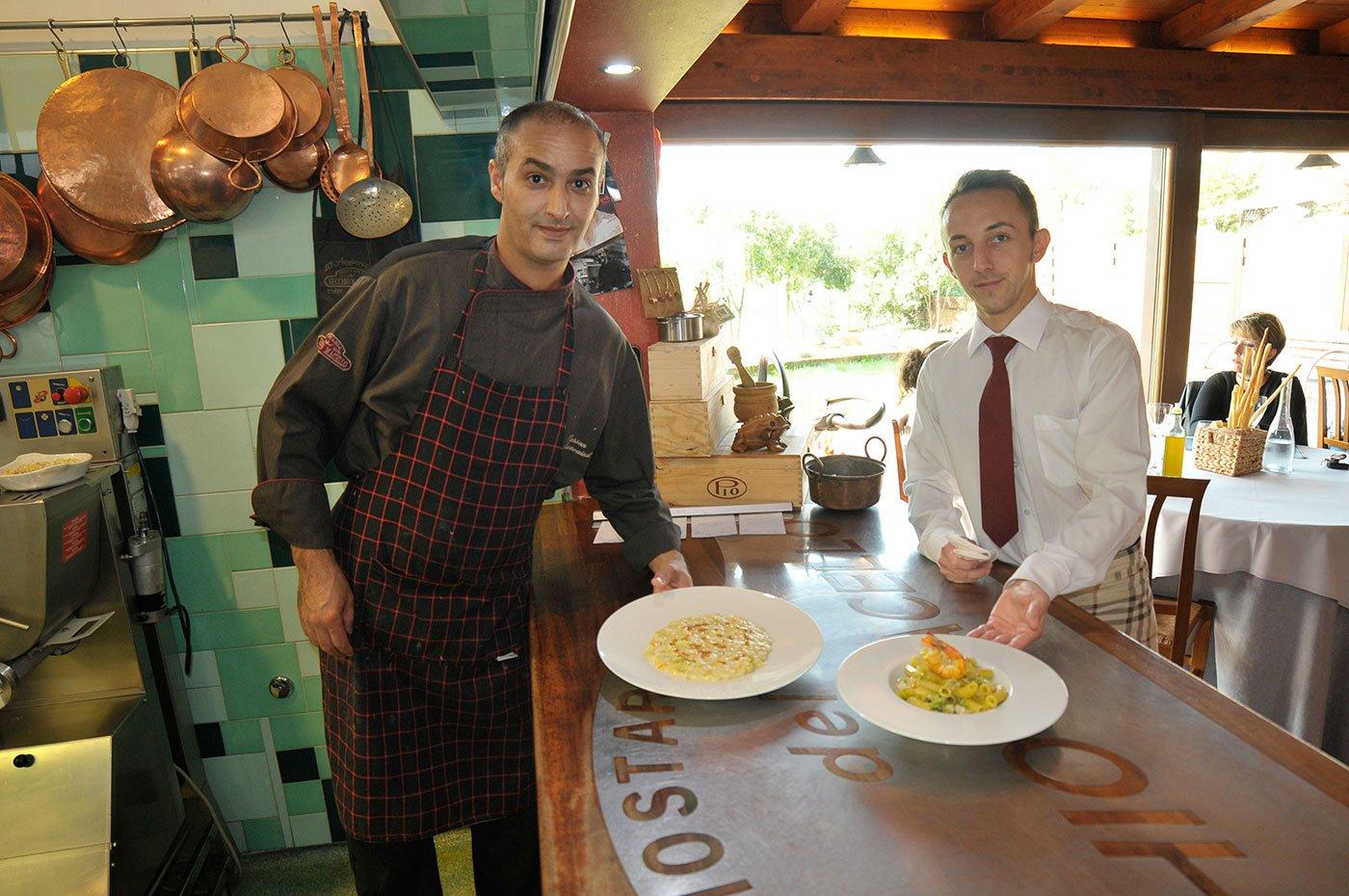 Due membri del personale del ristorante mentre mostrano due piatti di pasta