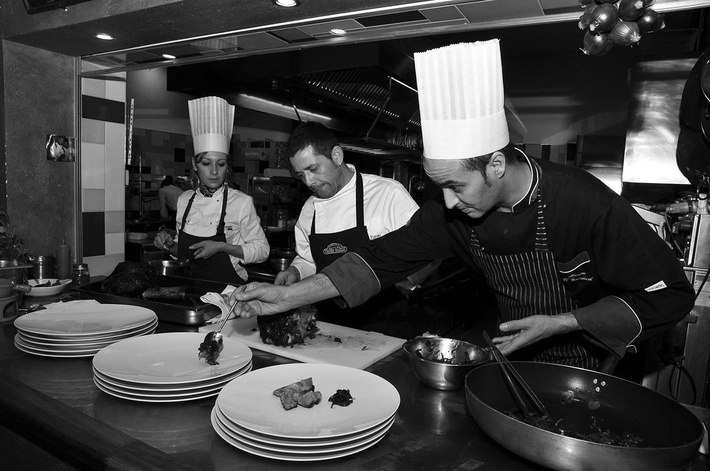 Tre cochi in una cucina durante preparano dei piatti