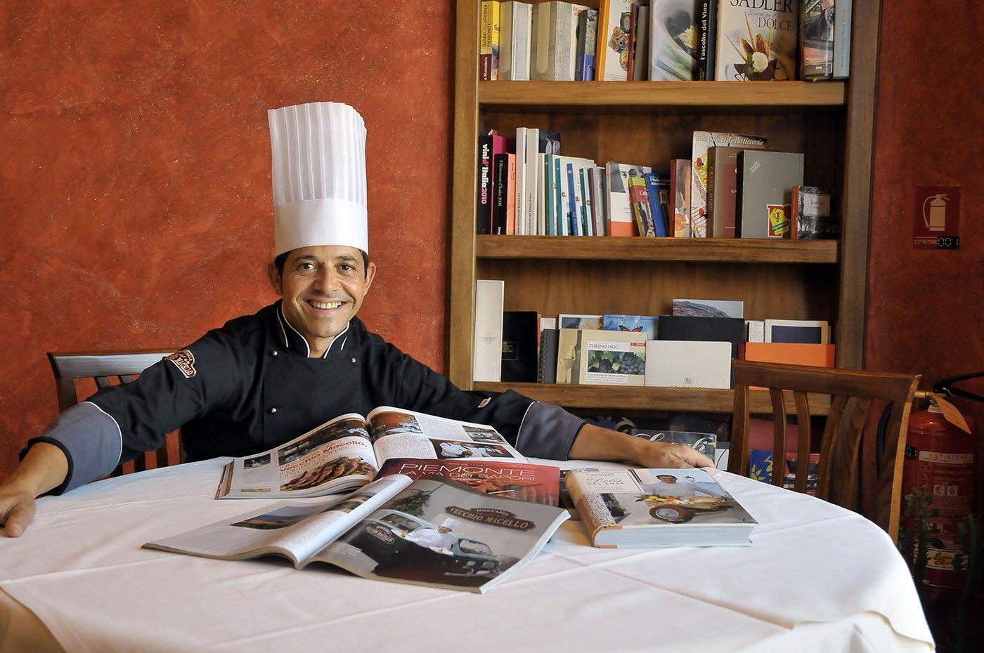 Un cuoco seduto al tavolo con delle riviste aperte