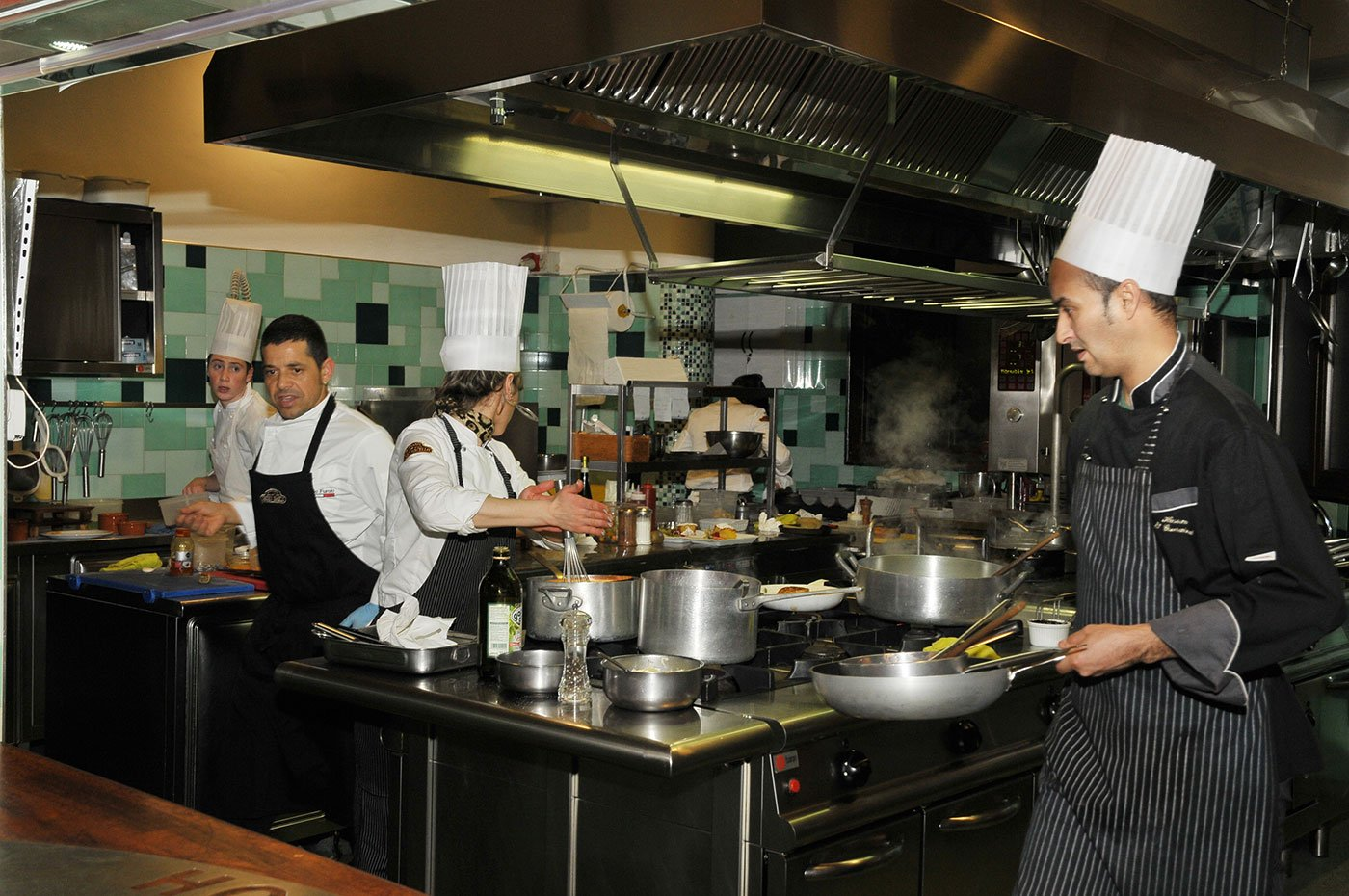 Dei cuochi in una cucina con dei grembiule