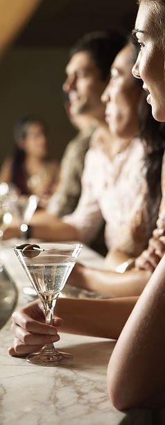 Delle persone al banco con dei bicchieri