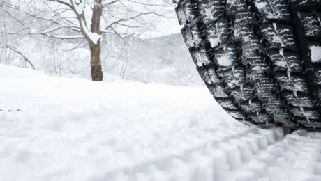 View of winter tire on snow. City Driving School offers winter driving clinics.